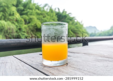 Half of orange juice glass on the table of the natural background