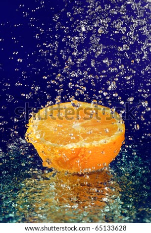 Half of orange with stopped motion water drops on deep blue