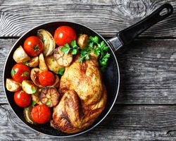 half of roast chicken in a skillet with roasted potato, fresh tomatoes, peppers and herbs on a rustic wooden table, horizontal view from above, close-up, flat lay