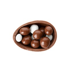 Half of tasty chocolate egg with candies on white background, top view