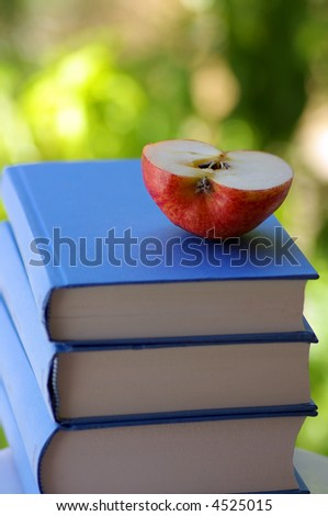 Half of the apple on books.