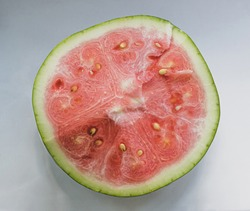 half of unripe watermelon with white seeds on white background