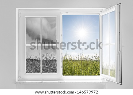 Half open window with view to the outside half on gray storm and half on clouds in blue sky with sun
