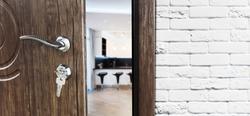 Half opened door to a kitchen. Door handle, door lock. Dining room door half open. Opening door. Welcome concept. Entrance to the room. Door at white brick wall, modern interior design.