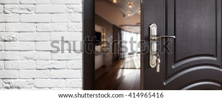 Half opened door to a living room. Door handle, door lock. Lounge door half open. Opening door. Welcome, privacy concept. Entrance to the room. Door at white brick wall, modern interior design.  #414965416