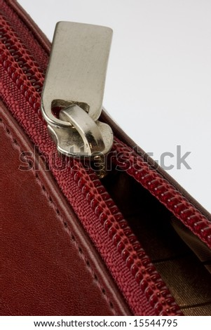 half opened zipper on a red leather bag