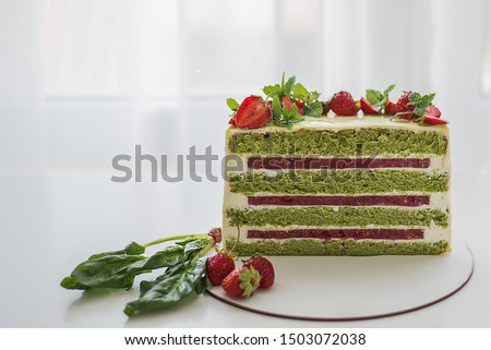 Half or slice of delicious fresh cake  on white background.  strawberries cake.strawberry cake with spinach. green cakes with strawberry layer and cream. sponge cake