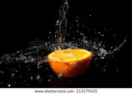 half orange with splashes of water on a black background