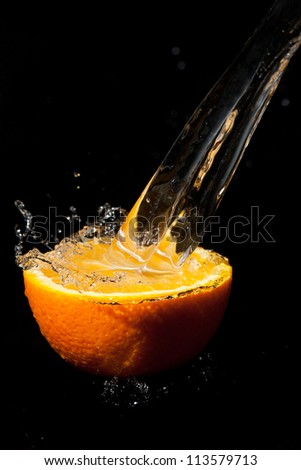 half orange with splashes of water on a black background - stock photo