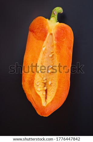 Half papaya on a black isolated background. Top view, flatlay