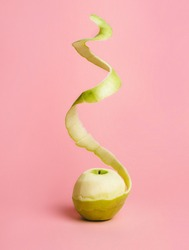 Half peeled fresh green apple with flying peel on pastel pink background. Creative fruit concept with copy space. Surreal food composition.