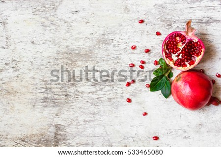 half pomegranate and ripe pomegranate fruit with seeds on white wooden rustic background. top view.