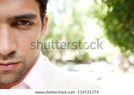 Half portrait close up of a young and attractive businessman's face looking at camera with a leafy background.