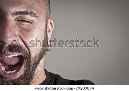 Half portrait of a man who winks on grey background - stock photo