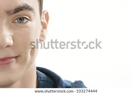 Half portrait of teenager looking at camera and smiling on a white background.