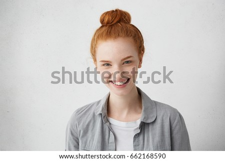 Half profile of young lady with blue eyes, ginger hair knot and freckled skin having fascinated smile rejoicing her achievements. Glad good-looking woman with pale cheeks and frail constitution