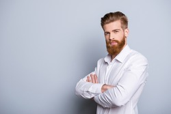 Half-profile portrait of serious confident bearded man keeping  crossed hands near copy space and looking at camera