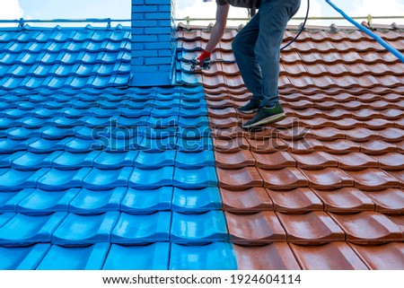 Half roof painted in blue, half of tiles are still red. Chimney is painted also. Before and after. Work at height.