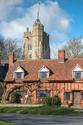 Half-timbered cottage with St. Mary the Virgin's Church on the village green. Cavendish, Suffolk, East Anglia, UK.