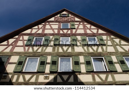 Half timbered house with green and red timbers and a blue sky