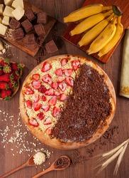 Half to half pizza strawberry with white chocolate and banana with chocolate - Traditional brazilian pizza de morango com chocolate branco e banana com chocolate - Top view.