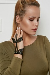 Half-turn portrait of lady, wearing olive sweater with boat neckline. The girl with her eyes closed is wearing leather slave bracelet with silver studs and perforated insertions in view of wings.