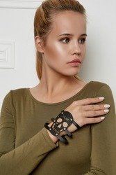 Half-turn portrait of lady with fair hair, wearing olive sweater with boat neckline. The girl is looking to side, wearing leather slave bracelet with silver studs and wide insertion in view of skull.