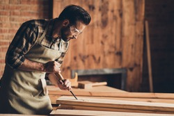 Half turned photo portrait of serious focused concentrated thoughtful handsome bearded strong masculine busy professional foreman builder using equipment wooden plank