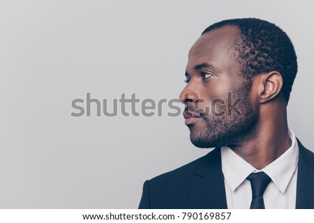 Half-turned side profile close up view portrait of handsome virile masculine attractive confident smart intelligent clever african man looking aside weairng smartsuit isolated on gray background