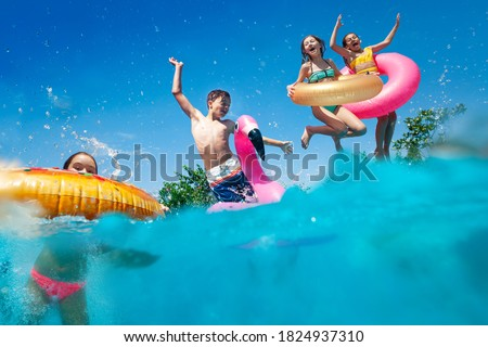Half underwater split image of many little kids dive in the swimming pool throw inflatable toys lifting hands have fun