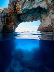 Half underwater, under the arch of Cala Goloritze. Gulf of Orosei the beautiful sea of Cala Goloritzè with the shape of the stone arch over and under the sea.