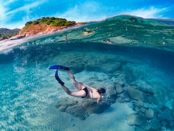 Half underwater view of a young woman diving deep into the sea water with mask and flippers. Amazing half underwater panorama. Cala Sinzias, Sardinia.