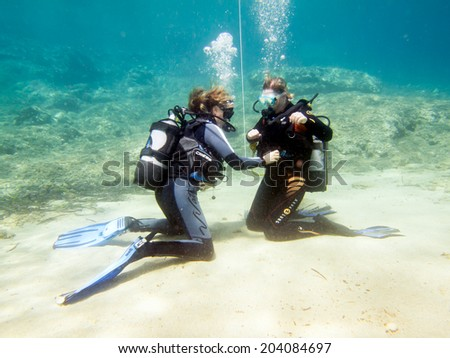 HALKIDIKI,GREECE-JULY 09 2014 : Two female scuba divers practise their skills underwater before a dive.Scuba diving is a sport carried out in many places around the world #204084697
