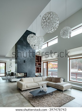 Hall in a modern style with light walls and big white round decorative lamps at the top. In the centre there is a beige sofa with pillows and plaid, dark table with three decorative vases, two black #397478743