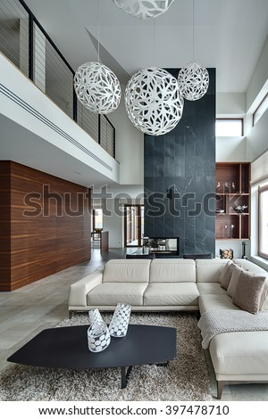 Hall in a modern style with light walls and big white round decorative lamps at the top. There is a beige sofa with pillows and plaid, dark table with three decorative vases, two black armchairs