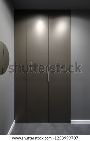 Hall in a modern style with luminous lamps, gray walls with white plinths and a tiled floor. There is a round mirror, brown lockers. Vertical. #1253999707