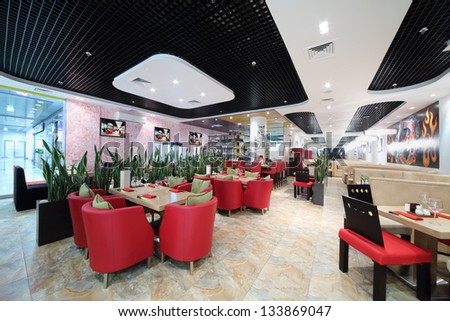 Hall Of Japanese Restaurant With Wooden Tables, Red Armchairs And Green Leaves.