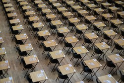 Hall with empty wooden desks and plastic chairs, ready to be used for examination purposes.