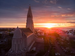 Hallgrimskirkja church in Reykjavik during sunset with flying birds in background, Iceland, most beautiful church in the world, drone aerial shot - Image, amazing view on Icelandic capital