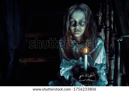 Photo of  Halloween. A ghost girl in a nightgown wanders through the old house at night.