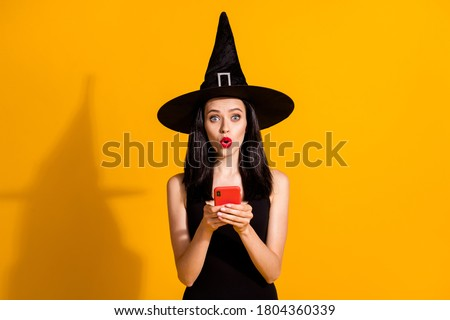 Halloween almost canceled. Photo of cute lovely young magician lady hold telephone amazed theme event postponed wear black wizard headwear dress isolated bright yellow color background