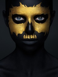 Halloween and creative make-up theme: beautiful girl model with black body with gold mask skull paint on dark background in studio