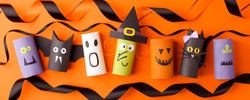 Halloween and decoration concept - monsters from toilet paper roll tube on orange. Simple easy diy creative idea. Eco-friendly reuse recycle decor, kindergarten paper craft, seasonal holiday banner
