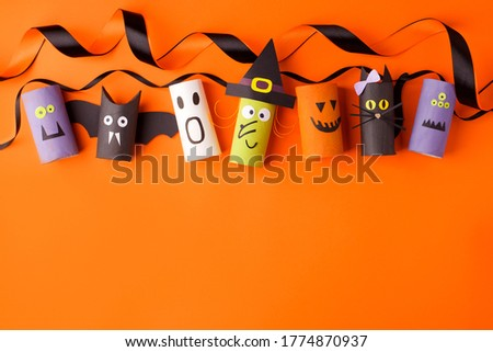 Halloween and decoration concept - monsters from toilet paper roll tube on orange. Simple easy diy creative idea. Eco-friendly reuse recycle decor, kindergarten paper craft, seasonal holiday banner Сток-фото ©