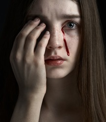 Halloween and horror theme: portrait of a sad girl with tears of blood on a dark background in the studio