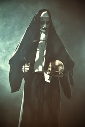 Halloween and Horrors. Devilish evil nun with a skull and sickle in her hands. Smoky background.