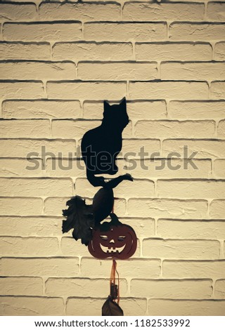 Halloween animal totem. Mystery and superstition concept. Holiday celebration symbol. Black cat and orange pumpkin with tree leaves silhouettes paper cutouts on beige brick wall. #1182533992