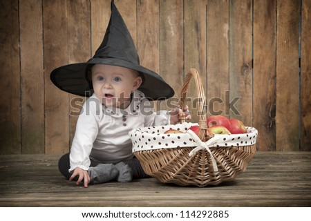 halloween baby with basket of apples, seated on an old wooden floor