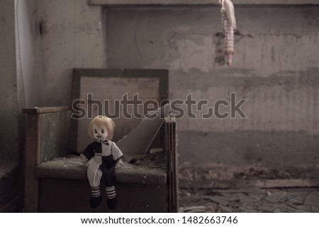 Halloween background A terrible harlequin doll sitting in a chair, a second doll hangs on a second background. Theme for horror. Mystical art photography. The concept of loneliness, abandonment #1482663746