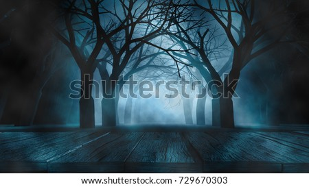 Shutterstock Halloween Background concept Spooky forest volumetric fog with many dead trees and wooden table foreground.3d rendering